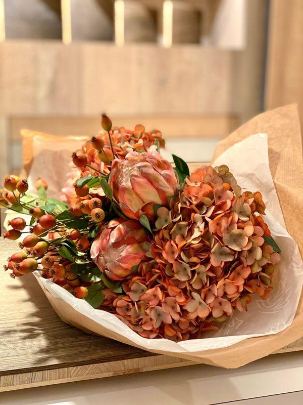 Precioso bouquet de proteas, hortensias y bayas tono melocotón.