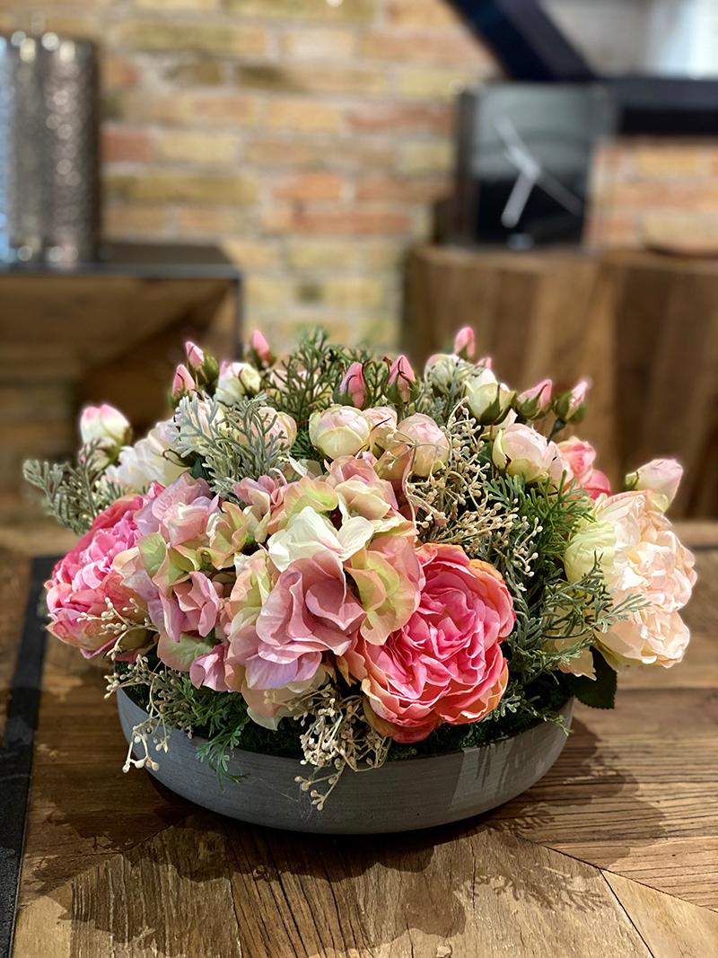 Todas las flores que te gustaría tener de jardín en tu mesa. centro de mesa con hortensias, rosa inglesa, y rosas de pitiminí, en base de piedra redonda.